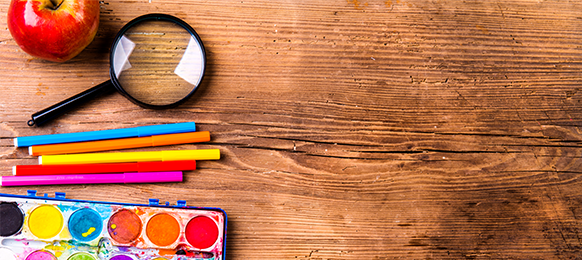 Colorful school supplies on a wood surface