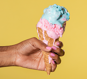 Hand holding an ice cream cone against a yellow background